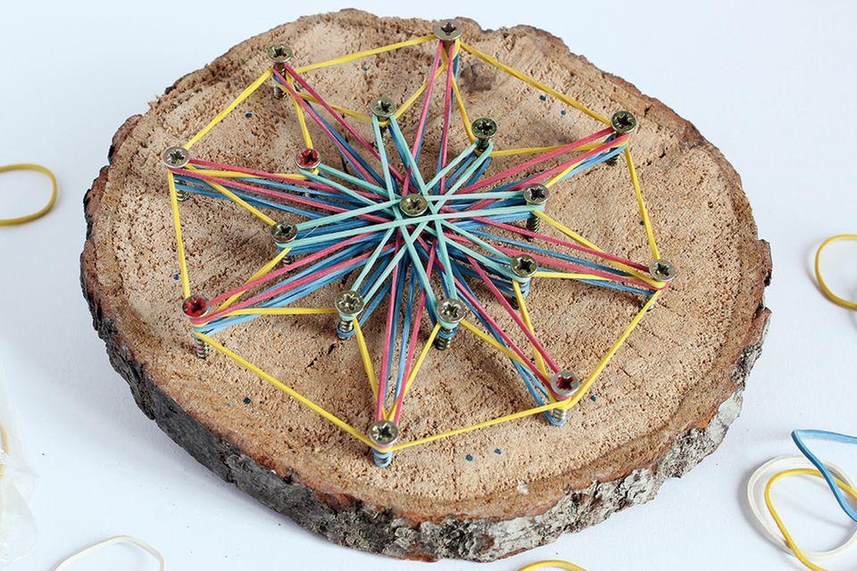 Mandala aus Holz und Gummibändern