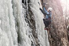 Eiskletterer klettert an einem gefrorenen Wasserfall, Alpbach, Alpbachtal