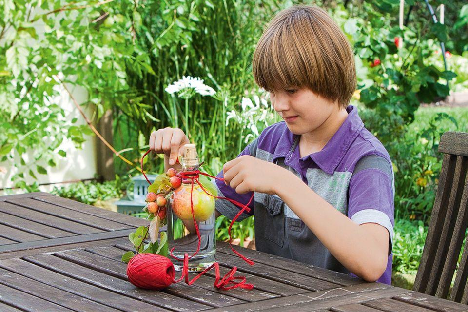 Junge zieht Apfel in der Flasche