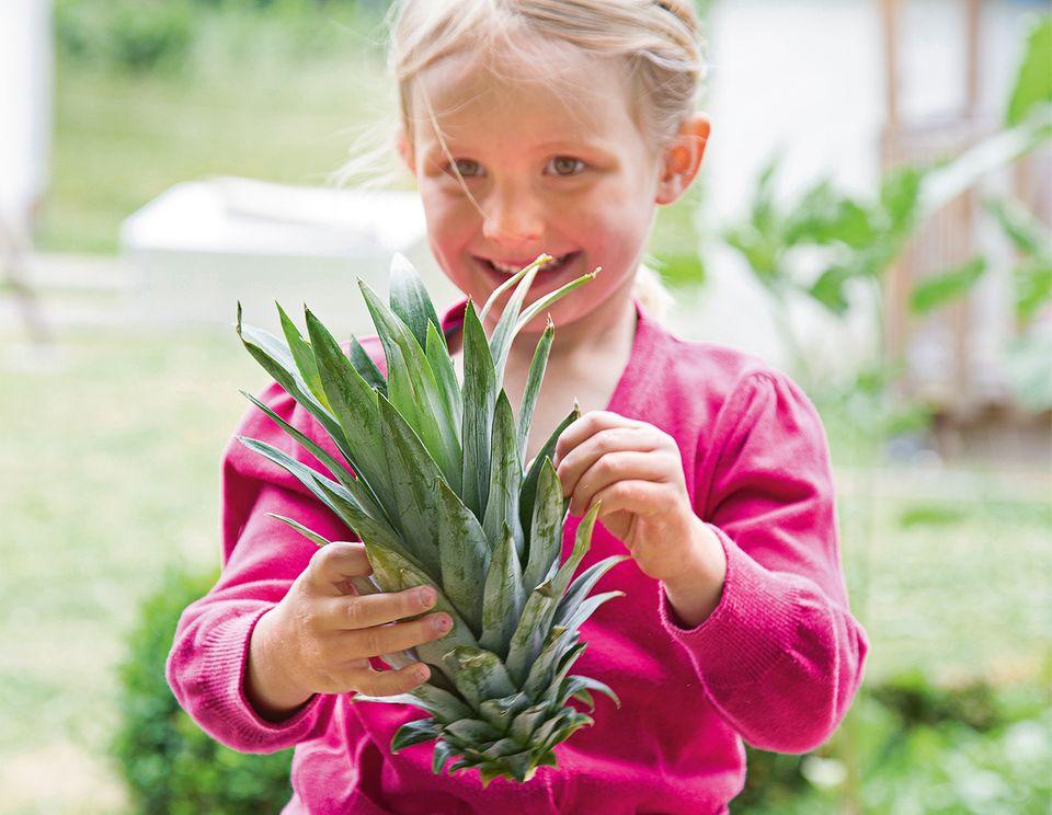 Mädchen hält eine Ananaspflanze in der Hand