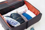 Gerollte Kleidung im Koffer