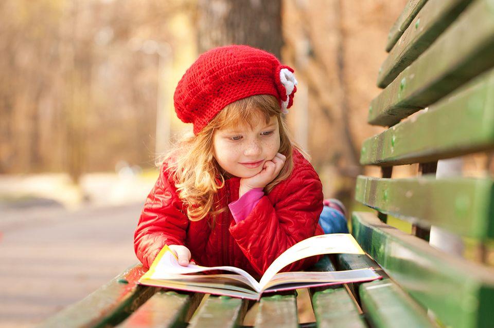 Mädchen liest auf einer Parkbank
