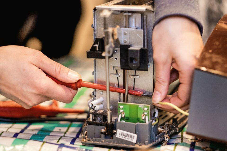 Toaster wird mit Schraubenzieher repariert