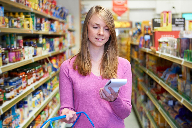 Mädchen mit Einkaufszettel im Supermarkt