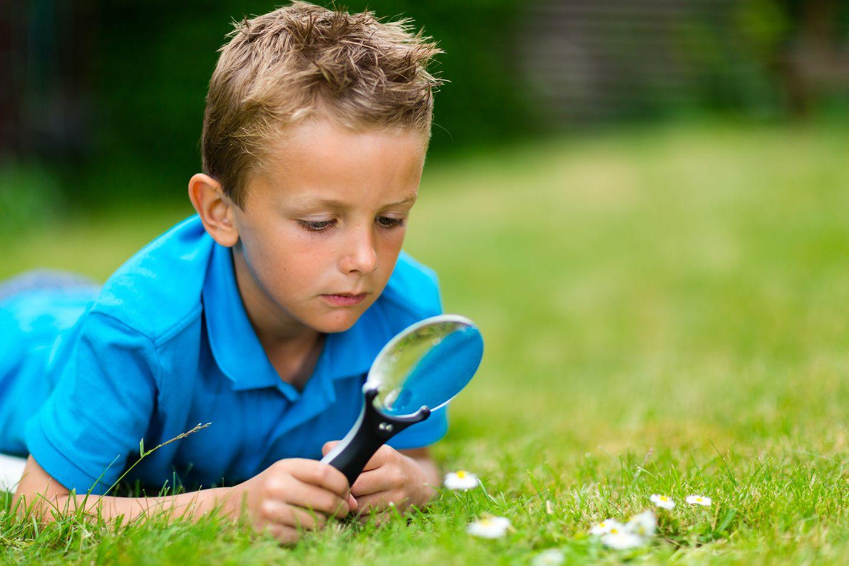 Junge mit Lupe im Gras