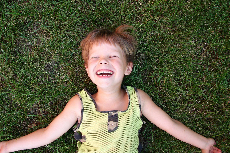 Lachender Junge im Gras
