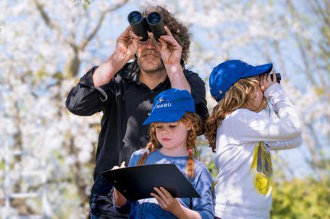Familie beobachtet Vögel mit Fernglas