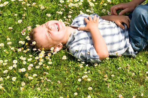 Junge liegt lachend auf der Wiese