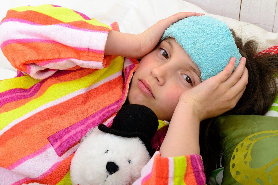 Mädchen mit Kopfschmerzen im Bett