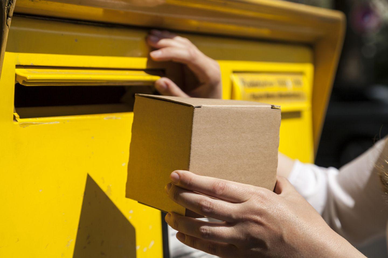 Frau versucht kleines Päckchen in Briefkasten zu werfen