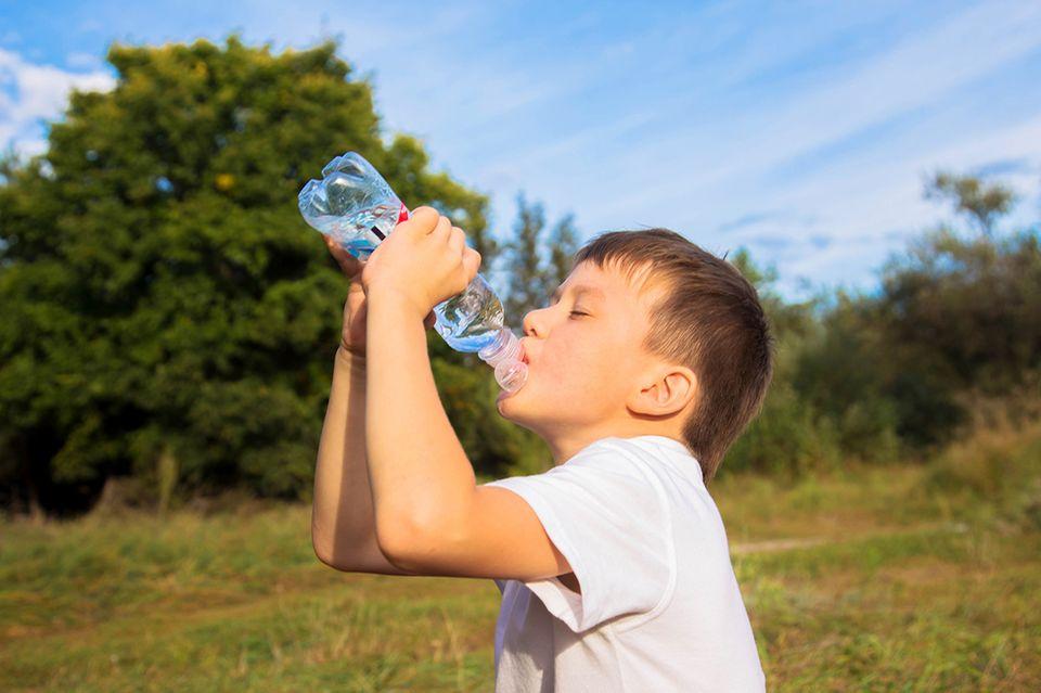 Junge trinkt aus einer Wasserflasche