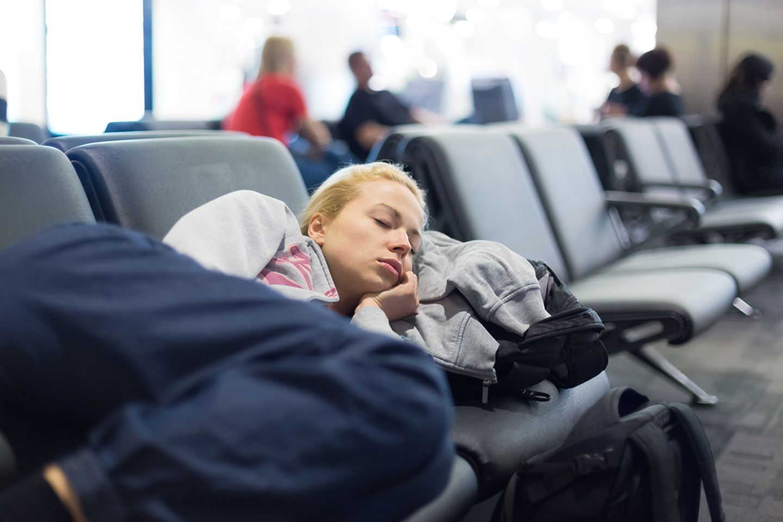 Frau schläft am Flughafen