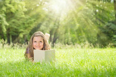 Mädchen liest auf der Wiese