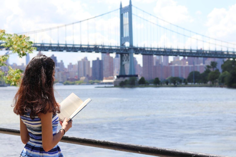 Frau liest Buch vor Brooklyn Bridge