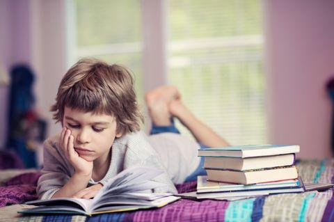 Jung liest auf dem Bett