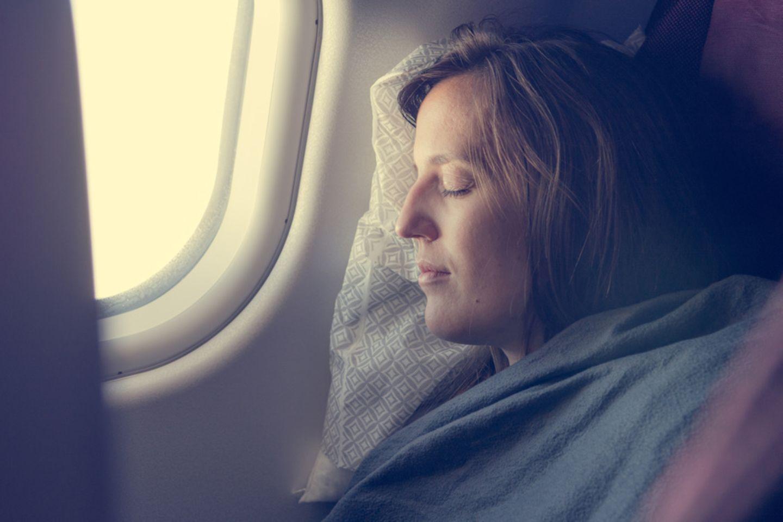 Frau schlafend im Flugzeug