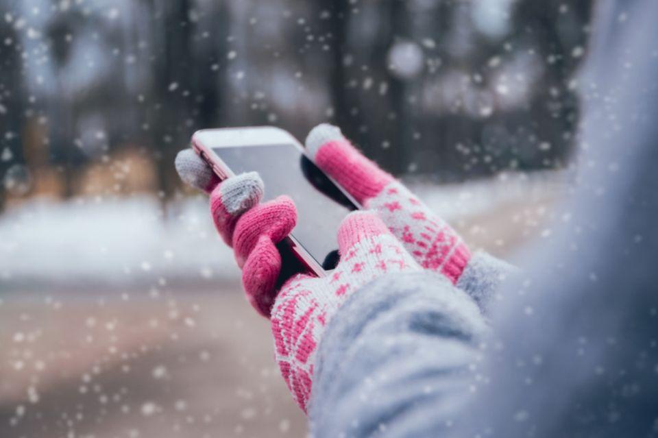 Smartphone wird mit Handschuhen bedient
