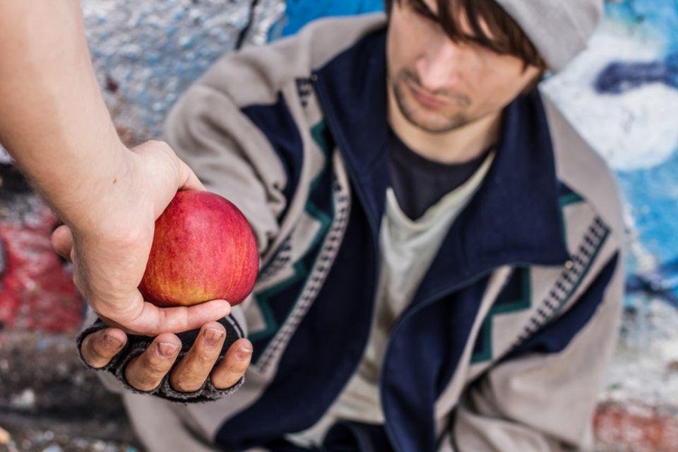 Obdachloser Mensch bekommt einen Apfel gereicht