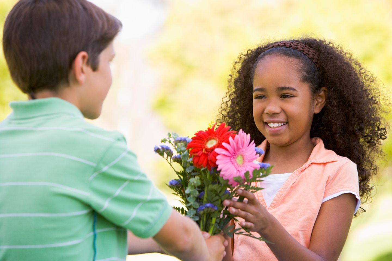 Junge schenkt Mädchen Blumen