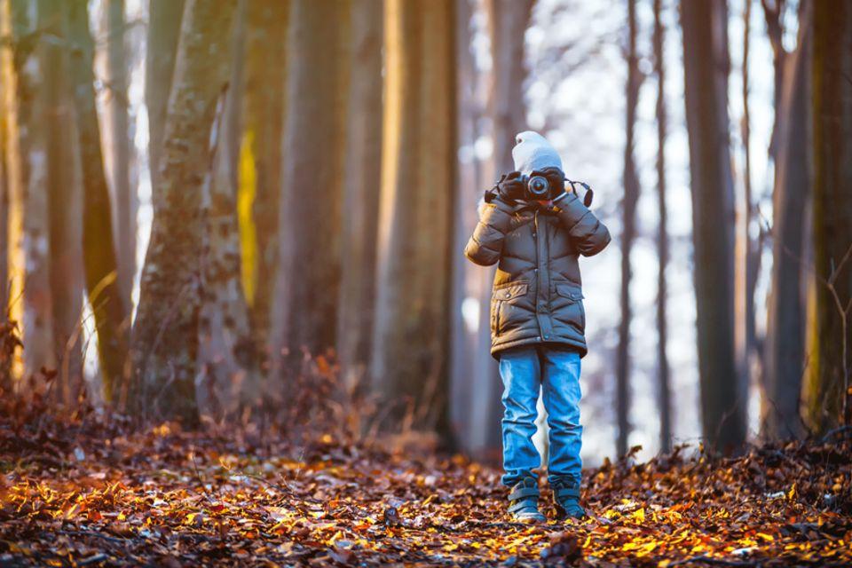 Junge fotografiert im Wald