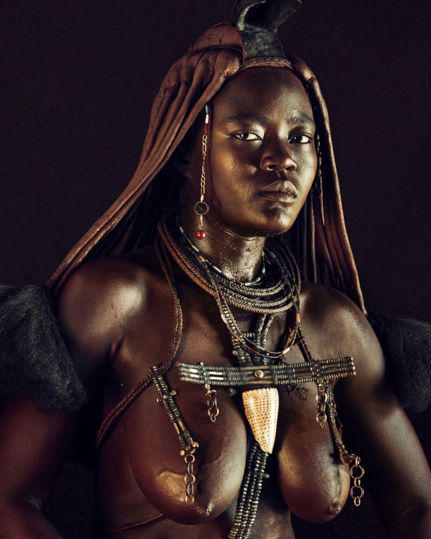 Die Otjize-Paste, hergestellt aus Butterfett und  Ockerpigment, parfümiert mit dem Harz einer Myrrhenart, schützt die Himba vo…