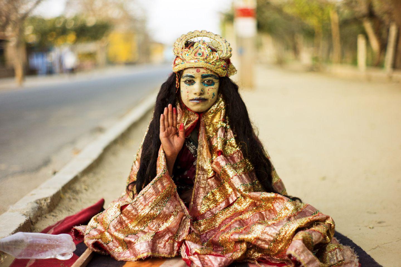 Eine junge Krishna-Anhängerin segnet Pilger auf dem Weg rund um den Govardhana-Hügel
