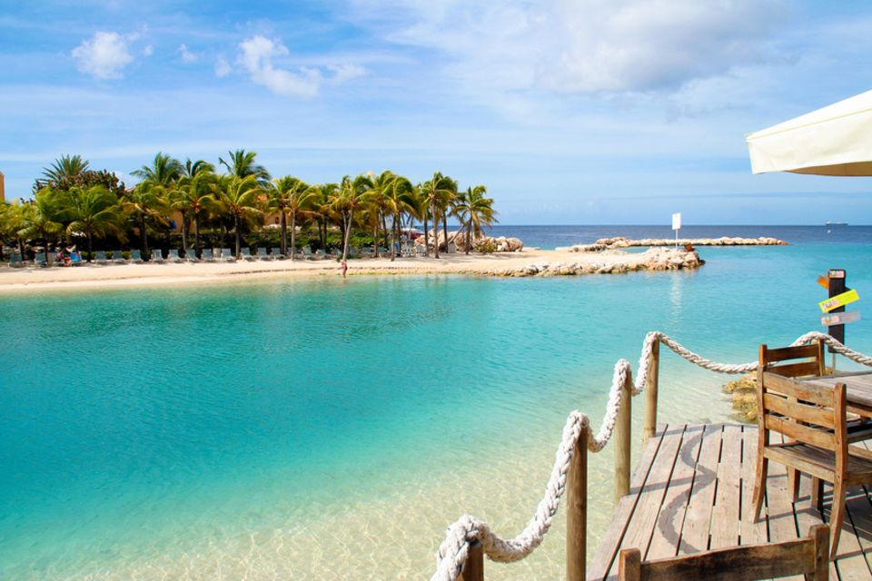 Reisetipps: Blick auf Mambo Beach: Der weiße Sandstrand mit den Kokospalmen gehört zu den bekanntesten Stränden der Karibikinsel Curacao