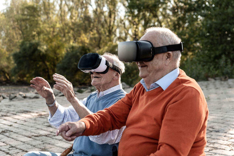Zwei alte Freunde sitzen am Flussufer mit VR-Brille