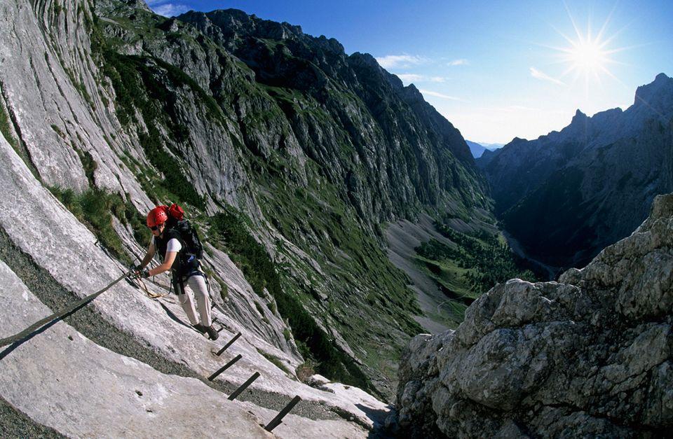 Bergsteigerin auf dem Klettersteig zur Zugspitze, Höllental, Deutschland