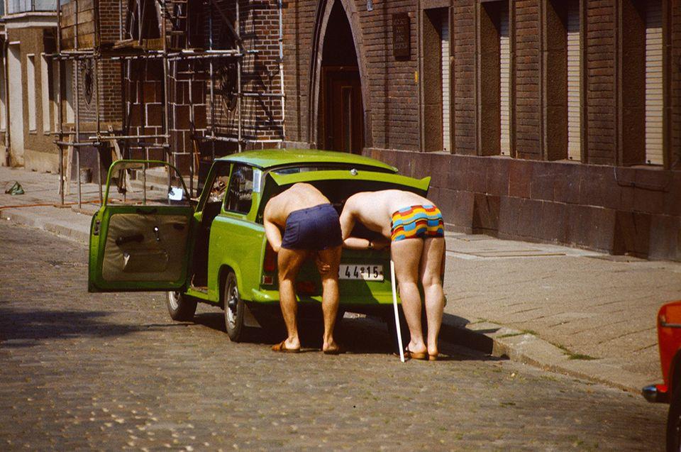 DDR: Maenner in Badehose beugen sich in den Kofferraum eines Trabant