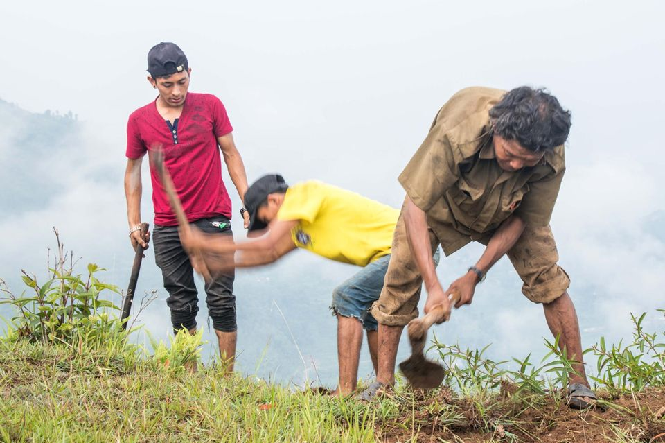 Mit einfachen Hacken bearbeiten Dorfbewohner den Boden, den der Monsunregen schon angefeuchtet hat