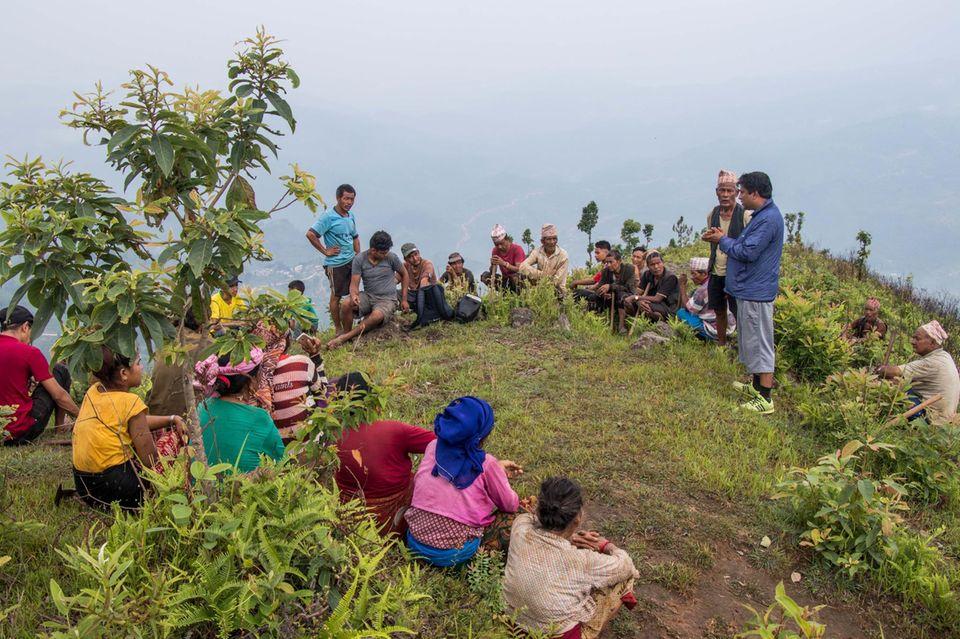 Ein Forstexperte erklärt den freiwilligen Helfern die verschiedenen Schritte der bevorstehenden Aufforstung