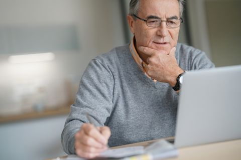 Älterer Mann sitzt am Laptop