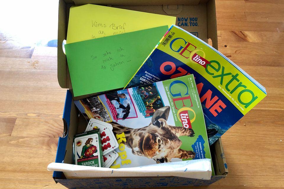 Briefe, Magazine und ein Spiel in einer Kiste