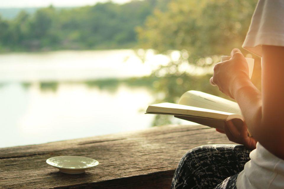 Frau trinkt Kaffee am See