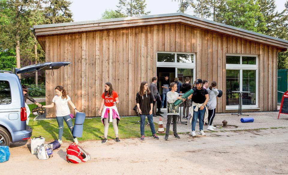 Die Schülerinnen und Schüler laden Isomatten und Schlafsäcke aus dem Elternauto aus.