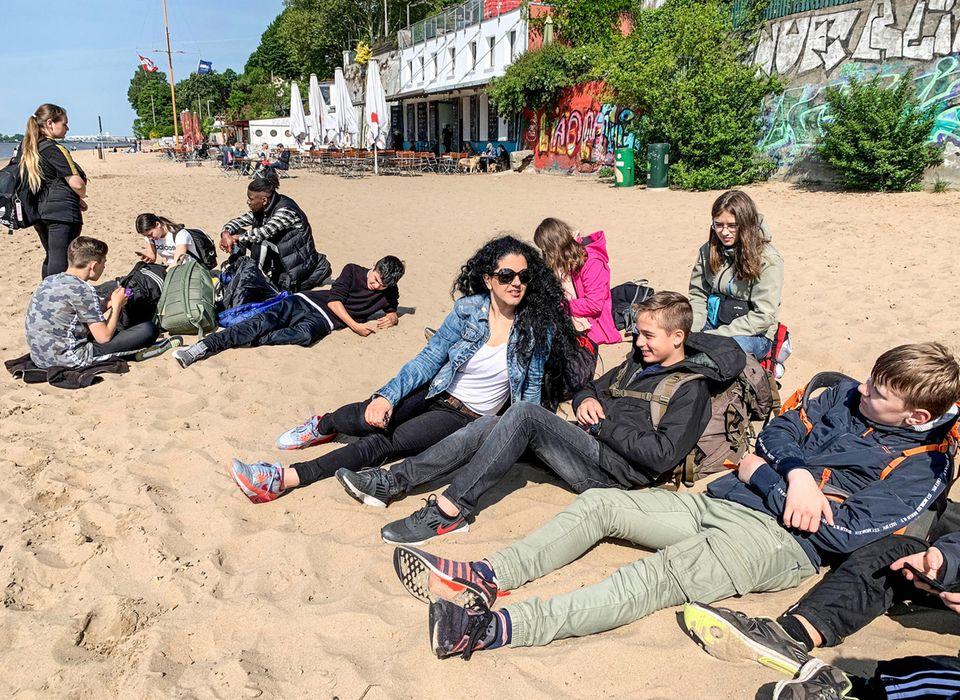Geschafft! Am Ende der Reise entspannt die Klasse am Hamburger Elbstrand in der Sonne