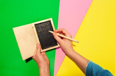 Eine Schreibtafel auf grün-rosa-gelbem Untergrund