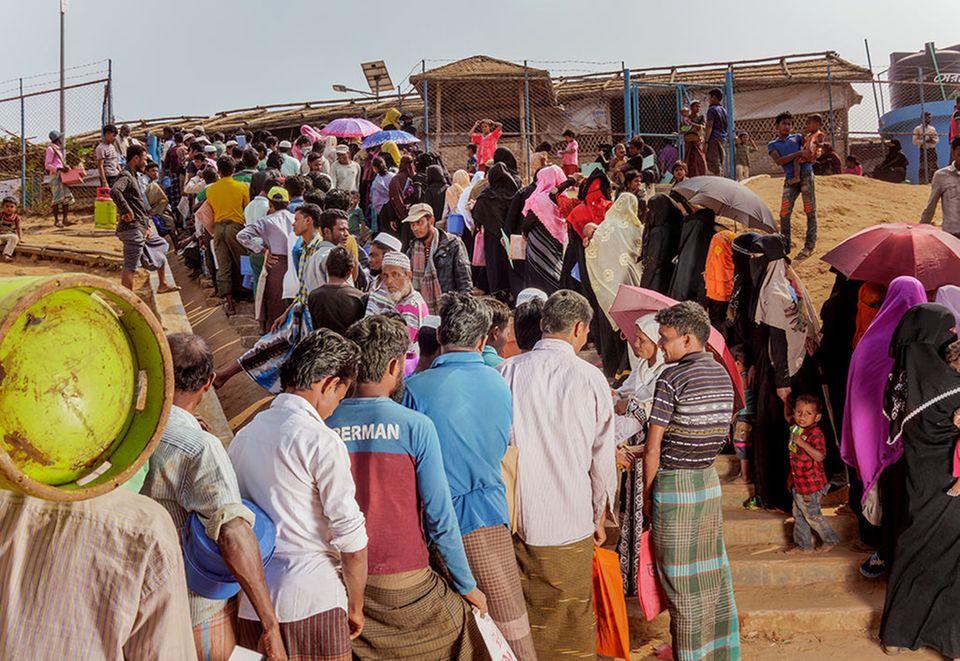 Bangladesch: Vor einer Nahrungsmittelausgabestelle warten Männer und Frauen getrennt. Für jede Nachbarschaft gilt ein anderer Abholtermin