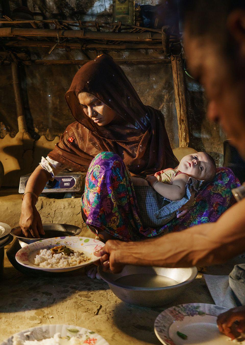 Bangladesch: Die Rohingya Arafa Begum serviert ihrem Mann Essen. Die kargen Vorräte lagern auf einem Holzgestell über dem Gaskocher