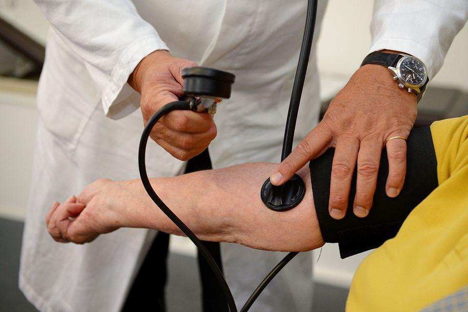 (Fast) nur noch Covid?: Stuttgart: Ein Arzt misst in einer Praxis einer Patientin den Blutdruck