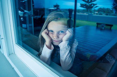 Mädchen isoliert hinter der Fensterscheibe