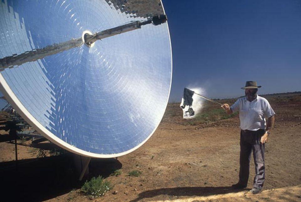 Gewölbte Spiegel in einem Solarkraftwerk. Sie lenken die Sonnenstrahlen zur Mitte. Eine Schüssel liefert so viel Energie, dass ein Stofflappen davor sofort in Flammen aufgeht