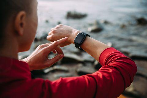 Frau schaut auf ihre Smart Watch am Wasser