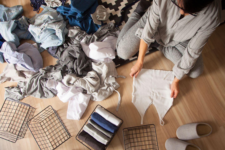 Frau beim Ausmisten des Kleiderschranks