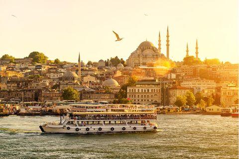 Traumziel der Woche: Wenn die Skyline von Istanbul bei Sonnenuntergang in warmen Goldtönen erstrahlt, macht das Goldene Horn seinem Namen alle Ehre. Wer am Abend am Ufer des Bosporus steht, die würzige-warme Luft einatmet und dabei den Blick über die Fähren auf dem glitzernden Wasser und die Minarette der Hagia Sophia und der Moschee Sultan Ahmet Camii schweifen lässt, begreift den ganzen Zauber, den Istanbul - einst Konstantinopel - seit 2600 Jahren verströmt.