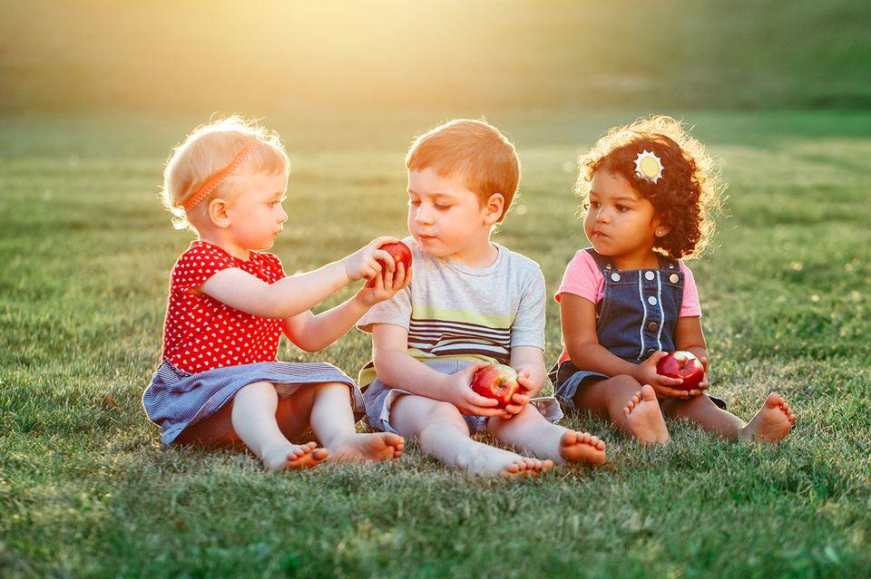 Drei Kinder sitzen auf einer Wiese und teilen Äpfel
