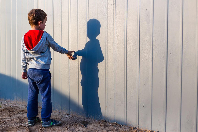 Ein Junge berührt seinen Schatten