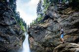 Mann betrachtet von einem Felsen aus den Buchenegger Wasserfall