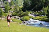 Wandernde Frau am Fluss in den Alpen